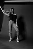 Schwarzweiss-Porträt des blonden Mädchens im T-Shirt und der Jeans auf dunklem Hintergrund wirft die Haarmodellversuche Stockfotografie