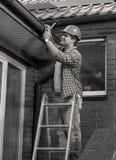 Schwarzweiss-Porträt des männlichen Tischlers Hausdach reparierend stockbild