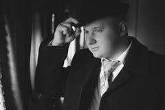 Schwarzweiss-Porträt des Mannes in der Melone, die heraus Zug schaut lizenzfreie stockfotos