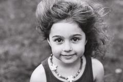 Schwarzweiss-Porträt des netten kleinen Mädchens, das draußen lächelt Lizenzfreie Stockbilder