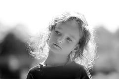 Schwarzweiss-Porträt des netten kleinen Mädchens, ernster Blick, gelocktes Haar, sonniges Sommerporträt lizenzfreie stockfotos