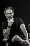 Schwarzweiss-Porträt des reifen erfüllten Mannes, der auf Stuhl sitzt lizenzfreie stockbilder