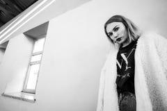 Schwarzweiss-Porträt einer stilvollen Frau, die gegen einen grauen Hintergrund beim Lügen gegen die Wand aufwirft Stockfotografie