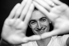 Schwarzweiss-Porträt eines jungen Mannes in einem T-Shirt, lächelnd und betrachten die Kamera durch seine Hände Lizenzfreies Stockfoto
