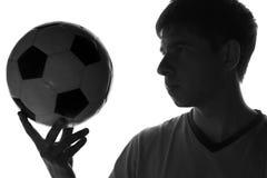 Schwarzweiss-Porträt eines jungen Mannes mit einem Fußball in seiner Hand Stockbild