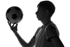 Schwarzweiss-Porträt eines jungen Mannes mit einem Fußball in seiner Hand Lizenzfreie Stockfotos