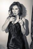 Schwarzweiss-Porträt schöner junger Dame mit einem Glas des Getränks auf hellem Hintergrund Stockfotografie