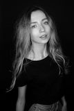 Schwarzweiss-Porträt von Blondinen eines barfüßig Mädchens in einem T-Shirt und in den Jeansmodellversuchen Lizenzfreies Stockfoto