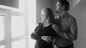 Schwarzweiss-Porträt von den jungen schönen Paaren, die aus Fenster heraus schauen Stockfoto