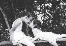Schwarzweiss-Porträt von zwei nettem wenig Mädchenlächeln und von pl Stockfoto