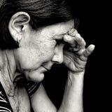 Schwarzweiss-Portrait einer sehr traurigen alten Frau Stockbild