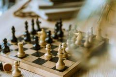 Schwarzweiss-Schach stellt auf Schachbrett am Tisch dar Stockfotografie