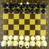 Schwarzweiss-Schachfiguren stehen auf einem Schachbrett vor Beginn eines Spiels, Draufsicht lizenzfreies stockfoto