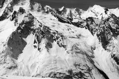 Schwarzweiss-Schnee bedeckte Berge mit Gletscher an der kalten Sonne Lizenzfreie Stockfotos