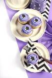 Schwarzweiss-Sparren mit purpurroter Themapartei-Mittagessentabelle mit kleinen Kuchen Stockfotos