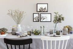Schwarzweiss-Stuhl bei Tisch mit Geschirr im grauen Esszimmerinnenraum mit Poster lizenzfreie stockfotos