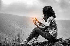 Schwarzweiss-Szene der jungen Asiatin sitzend auf dem Felsen an der Klippe und intelligentes Telefon verwendend stockbild