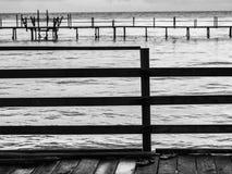 Schwarzweiss-Ton der Holzbrücke im Meer Stockfoto