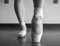 Schwarzweiss-Version des Abschlusses herauf die Ansicht eines Ballerinaballetttanzes, ihre Füße in der Ballettklasse aufwärmend Lizenzfreie Stockfotografie