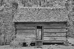 Schwarzweiss vom ursprünglichen Blockhaus in den rauchigen Bergen Lizenzfreie Stockfotos