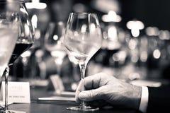Schwarzweiss vom Weißwein an Hand mit Abendessen auf Restaurant Stockbilder