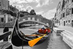 Schwarzweiss von einem schönen Kanal in Venedig mit selektiver Farbe auf der Gondel stockfotografie