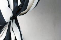 Schwarzweiss-Vorhang gebunden zurück zu anwesendem weißem Hintergrund lizenzfreie stockfotografie