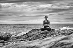 Schwarzweiss-Yoga auf dem Felsen bei dem Sonnenuntergang Lizenzfreie Stockfotografie