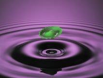 Schwebendes grünes Spritzen auf Purpur Lizenzfreie Stockfotos