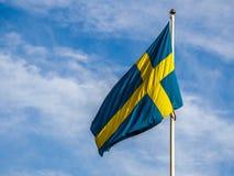 Schwedische Flagge, die im Wind durchbrennt Stockfotos
