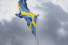 Schwedische Flagge, die im Wind durchbrennt stockfoto