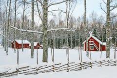 Schwedische Winterlandschaft mit roten hölzernen Häusern Lizenzfreie Stockfotos