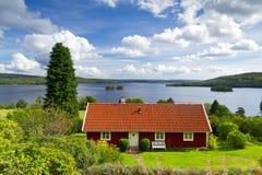 Schwedisches Häuschenhaus in dem See Lizenzfreie Stockfotos