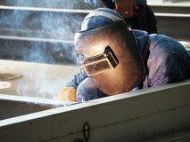 Schweißende Arbeitskraft mit schützendem Schweißen stockfotos