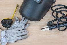 Schweißenskopf und Schutzausrüstung im industriellen Metallstahl auf hölzernem Hintergrund Lizenzfreies Stockbild