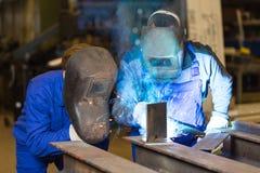 Schweißensmetall mit zwei Stahlbauarbeitern Stockbilder