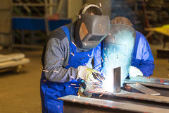 Schweißensmetall mit zwei Stahlbauarbeitern Stockfotografie