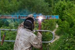Schweißer bei der Arbeit Schweißer kocht Metallgitter auf dem Grundlötlampe aus den Grund in der speziellen Kleidung und im Maske Stockfoto