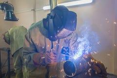 Schweißer in den gelben Handschuhen schweißt zwei Stücke des Stahlrohres unter Verwendung des elektrischen Schweißens stockbilder