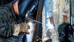 Schweißer an der Fabrik in schweißenden Maskenschweißungen asphaltieren Teile Feld Verdeckte schweißende Teile des Schweißers Sch lizenzfreie stockbilder