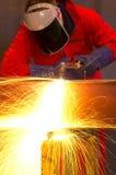 Schweißer verbiegt, um Metalllichtstrahl mit orange Funken zu schneiden. Lizenzfreie Stockbilder