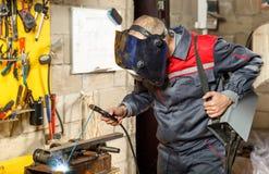 Schweißerarbeitskraft im Schutzmaskeschweißensmetall Lizenzfreie Stockfotos