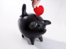 Schwein formte Moneybox, das mit Liebe geladen wurde Stockfotos