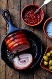 Schweinebratenbauchrolle mit Pfeffer, Seesalz, trocknete Rosmarin, Basilikum und Knoblauch auf einem Holztisch Rustikale Art Lizenzfreies Stockbild