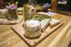 Schweinefett mit dem Knistern gedient mit Brot, sauren Gurken und roten Zwiebeln stockfotos