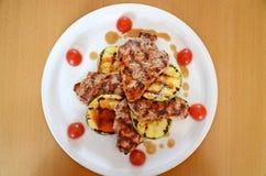 Schweinefilet mit Tomaten einer demi-glace Soße, der Zucchini und der Kirsche Lizenzfreies Stockfoto