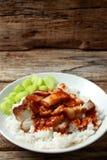 Schweinefleisch auf Reis mit roter Soße stockfotos