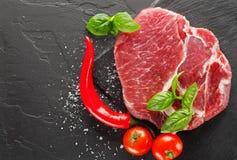 Schweinefleisch auf schwarzem Stein mit Pfeffer und Tomate Lizenzfreies Stockfoto