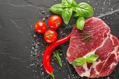 Schweinefleisch auf schwarzem Stein mit Pfeffer und Tomate Lizenzfreie Stockfotos