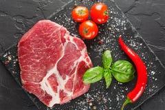 Schweinefleisch auf schwarzem Stein mit Pfeffer und Tomate Stockfotografie